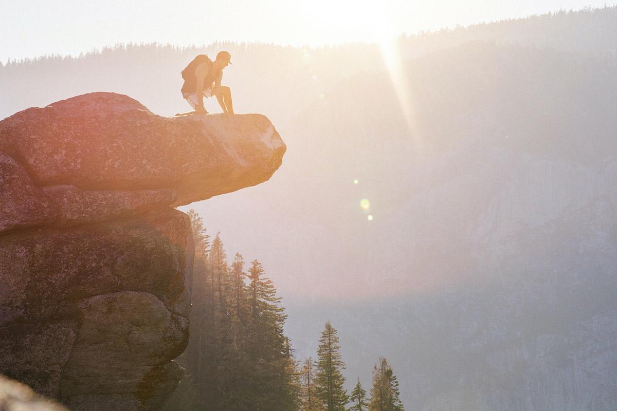 hiker on cliff sunset
